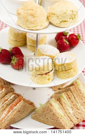Traditional British afternoon tea\ A cake stand containing various cakes and sandwiches as part of a traditional British afternoon tea