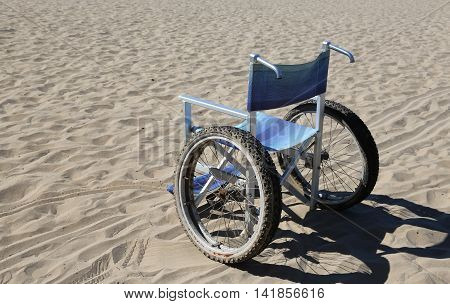 isolated wheelchair with special wheels on beach sand stock photo