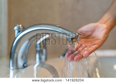 Woman taking a bath at home checking temperature touching running water with hand. Closeup on finger