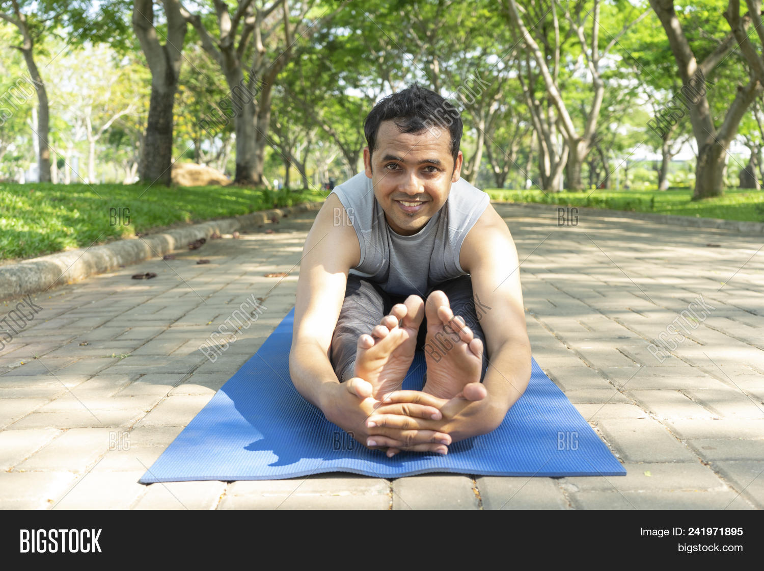 Smiling Young Indian Man Doing Seated Forward Bend Outdoors On Mat In Park With Trees In Background 241971895 Image Stock Photo