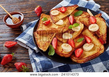 French toasts with appetizing, lacy brown crust and fluffy inside served on a black slate tray with fresh strawberries, banana slices, mint and honey, view from above, close-up stock photo