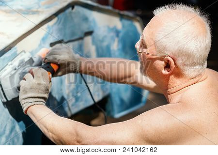 older man is repairing and grinding an old boat with a grinder stock photo