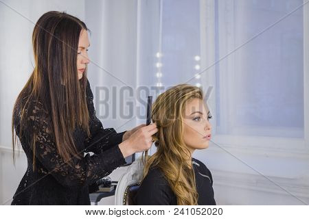 Professional hairdresser, stylist combing hair of female client in white make up room. Beauty and haircare concept stock photo