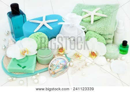 Bathroom and spa beauty treatment with orchid flowers, tea tree aromatherapy oil & soap, body foam wash, body lotion, moisturising cream, bath salts, sponges, flannels and seashells & pearls. stock photo