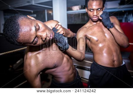 African American quick fighter punching in the chin his opponent during MMA fight stock photo