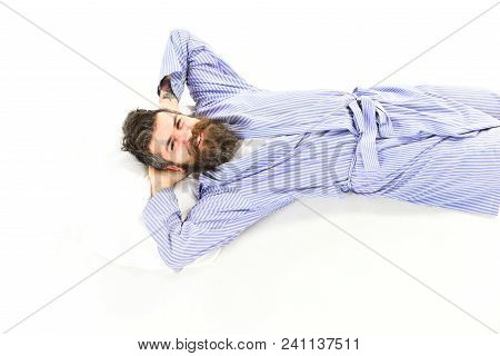 Slept well oncept. Man relax and having rest, white background. Man with smiling happy face wake up, lay on bed, put hands behind head, top view. Hipster with beard, mustache and messy hair slept well stock photo