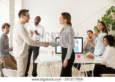 Smiling female boss promoting rewarding handshaking motivated worker showing respect while team applauding congratulating colleague at group meeting, appreciation and employee recognition concept stock photo
