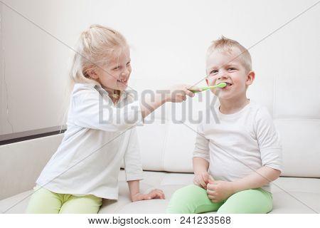 Little cute blonde girl is brushing the boy's teeth. Fun lifestile play dentist game. Children smile. Health care, dental hygiene stock photo