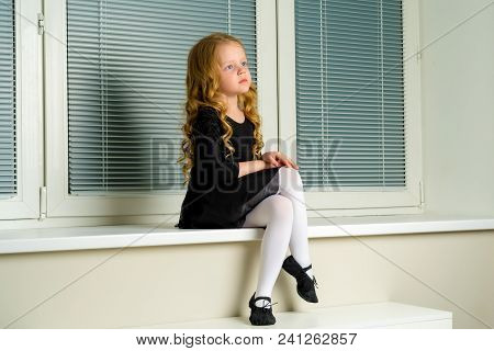A cute little girl is sitting on a window against a background of white horizontal blinds. Close-up. The concept of children, happy people. stock photo