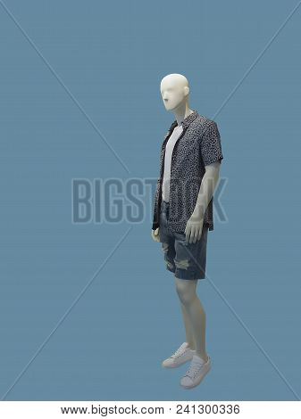 Full-length man mannequin dressed in short sleeve shirt and jeans shorts over blue background. No brand names or copyright objects. stock photo