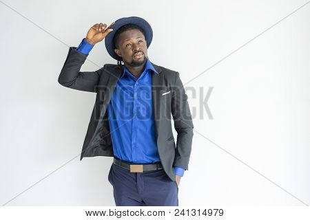 Pensive dreamy fashionable black man adjusting hat and looking up. Contemplative African businessman with beard thinking. Dreamlike concept stock photo