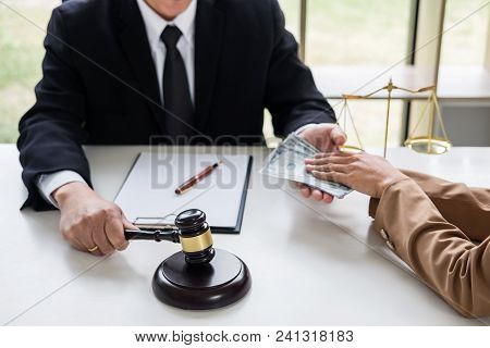 Bribery and corruption concept, bribe in the form of dollar bills, Businesswoman giving money to male lawyer while helps making deal to agreement a real estate contract and financial corporate. stock photo