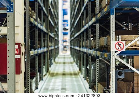 Defocused image of tiered storage facility at machinery industrial plant. Factory warehouse with spare parts. Shelves and rows. stock photo