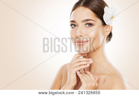 Woman Beauty, Face Skin Care and Natural Make Up, Girl with Orchid Flower in Straight Hair, Beautiful Makeup and Skincare stock photo
