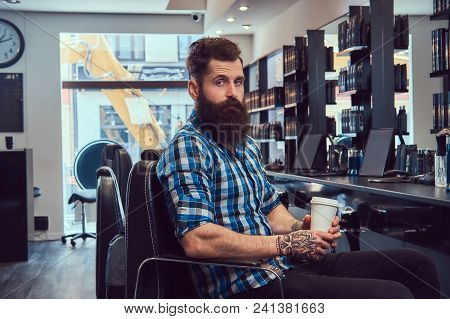 A handsome stylish bearded male with a tattoo on arm dressed in a flannel shirt drinks coffee in a barbershop. stock photo