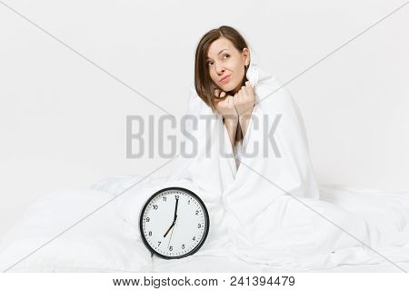 Young woman sitting in bed with round clock, white sheet, pillow, wrapping in blanket on white background. Beauty female wake up early in morning, spending time in room. Rest, good mood concept stock photo