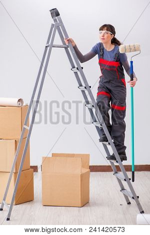 Woman painter painting in new apartment stock photo