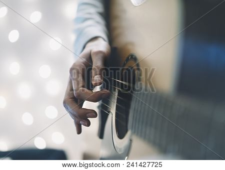 Сloseup of a man playing the guitar in a homelike atmosphere, sitting in a chair against a background of bokeh light horizontal stock photo
