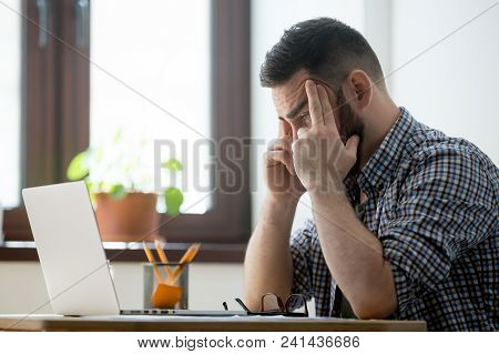 Frustrated businessman concerned male worker looking at laptop screen heavily thinking about problem solution, person evaluating taking risk, counting business success chances on market. Self control stock photo