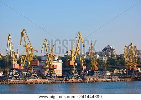 Wharf Cranes lifting cargo. Container cargo transportation by warf cranes. stock photo