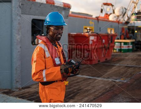 Seaman AB or Bosun on deck of offshore vessel or ship , wearing PPE personal protective equipment - helmet, coverall, lifejacket, goggles. He holds VHF walkie-talkie radio in hands. Cargo operations stock photo
