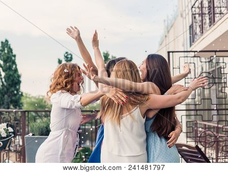 Girls Party. Beautiful Women Friends on the balcony Having Fun At Bachelorette Party. They are hugging in confetti with hands up stock photo