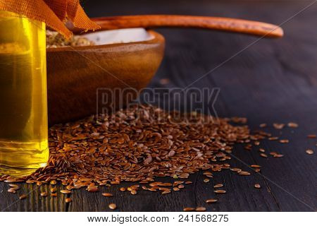 Brown Flax Seeds In Spoon And Flaxseed Oil In Glass Bottle On