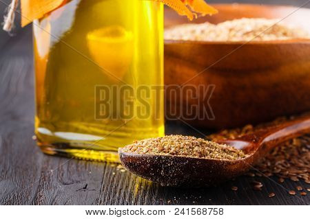 Brown flax seeds on spoon and flaxseed oil in glass jug on wooden table. Flax oil is rich in omega-3 fatty acid. stock photo