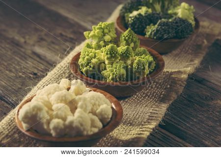 Fresh pieces of Romanesco broccoli, broccoli and cauliflower in small rustic wooden bowls. Selective focus on the Romanesco broccoli stock photo