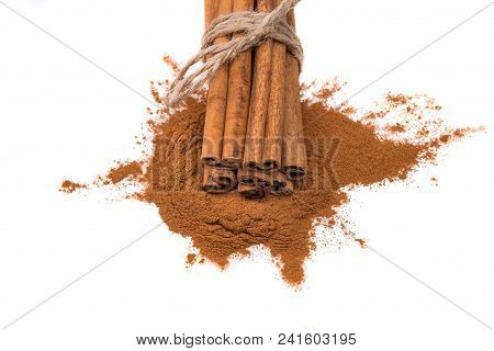 Cinnamon sticks tied with a rope on cinnamon powder, isolated on white background. stock photo
