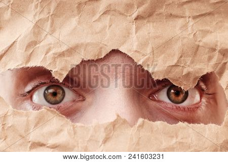 Eye looking through hole in paper. Spy eye watching through a hole. Eye looking through hole in old brown crumpled paper. stock photo