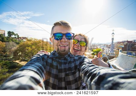 Travel couple happy making selfie portrait with smartphone in Park Guell, Barcelona, Spain. Beautiful young couple looking at camera taking photo with smart phone smiling in love. stock photo