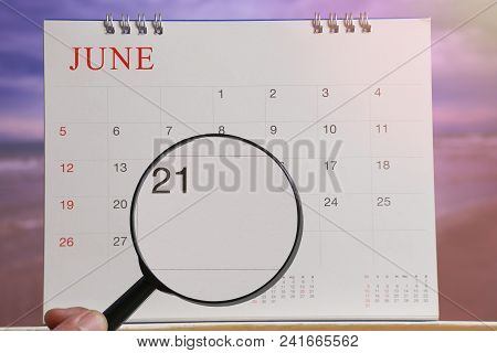 Magnifying glass in hand on calendar you can look Twentieth one day of month,Focus number twenty-one in June,Concept in business and meetings. stock photo