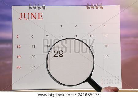 Magnifying glass in hand on calendar you can look Twenty-nine day of month,Focus number Twenty-nine in June,Concept in business and meetings. stock photo