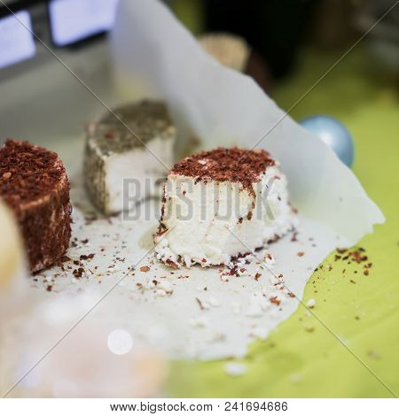Pieces heads of soft cheeses with different spices and additives on wooden market board. Gastronomic dairy produce, real scene in the food market, square stock photo