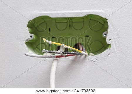 Unfinished electrical mains outlet socket with electrical wires and TV cable - connector installed in plasterboard drywall for gypsum walls in apartment is under construction and remodeling. stock photo