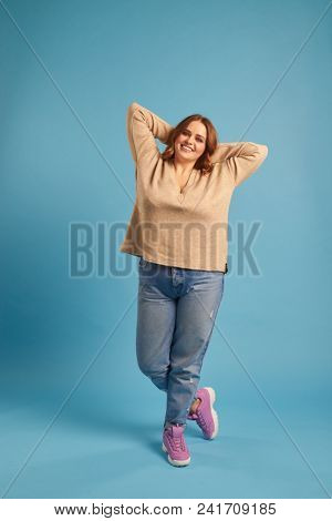 Joyful plus-size girl posing with arms above her head stock photo
