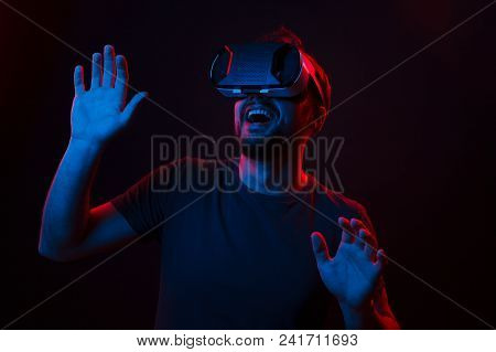 Handsome young man wearing VR headset and interacting with objects in virtual reality while standing on dark background. stock photo