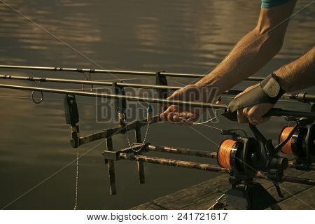 Rods, reels, lines and male hands on water background, fishing. Fishing equipment, gear, device. Angling hobby sport activity recreation stock photo