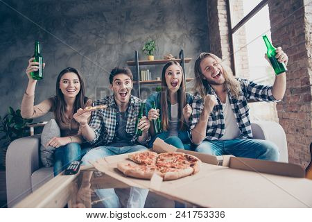 Yes, yeah, hooray! Cheerful jouful screaming yelling four soccer fans having day-off resting eating takeaway pizza and drinking beer stock photo