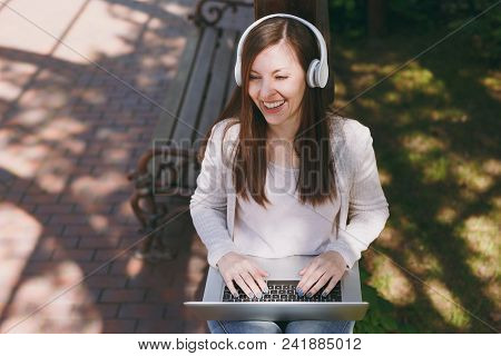 Young successful businesswoman in light casual clothes. Woman working on modern laptop pc computer, listen music in headphones on head in street outdoors. Mobile Office. Freelance business concept stock photo