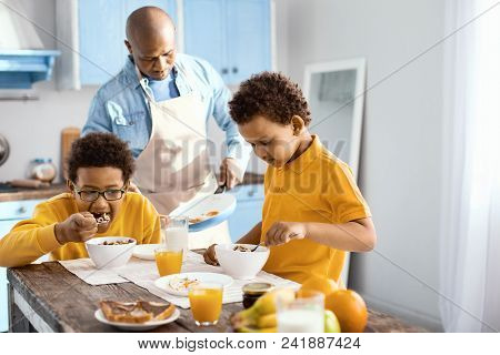 Delicious breakfast. Adorable little boys eating cereals for breakfast while their father in an apron cooking an omelet stock photo