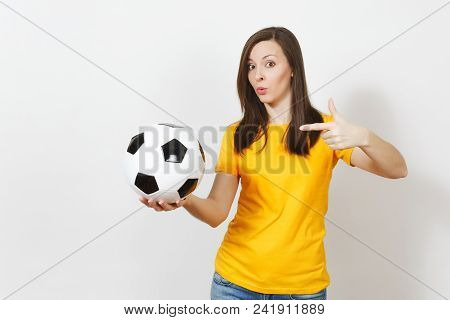Beautiful European young cheerful happy woman, football fan or player in yellow uniform pointing on soccer ball isolated on white background.   stock photo