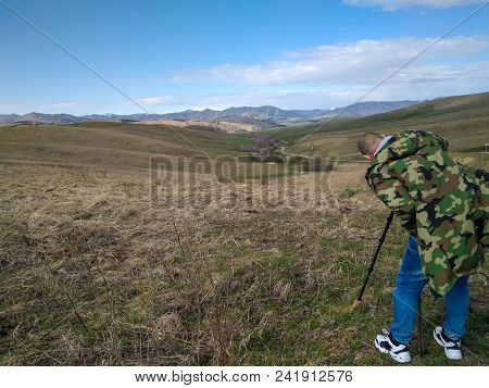 Young bald man in a military windbreaker jeans and white  sneakers takes pictures with a tripod of the Altai Mountains near the road. Backstage photo. stock photo