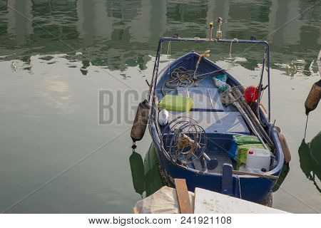 Small wooden fishing dinghy with ropes and tackle moored in a marina with reflections on the tranquil water stock photo