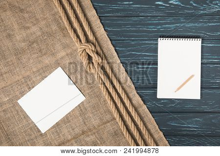 top view of empty paper on sackcloth with knotted rope and blank textbook with pencil stock photo