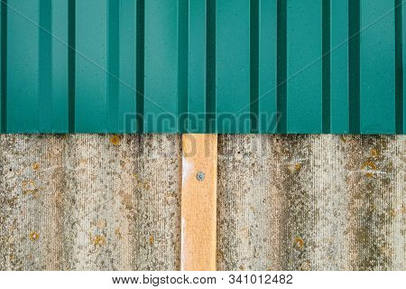 Repair of the old roof made of asbestos-cement sheets. Laying a metal profiled sheet with a fixing to wooden battens. stock photo