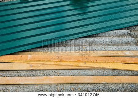 Repair of the old roof. Metal profiled sheet with and wooden battens lies on old roof made of asbestos-cement sheets. stock photo