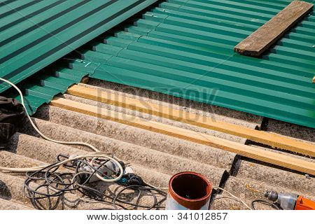 Repair of the old roof made of asbestos-cement sheets. Laying a metal profiled sheet with a fixing to wooden battens. Tools on installation professional sheet. stock photo