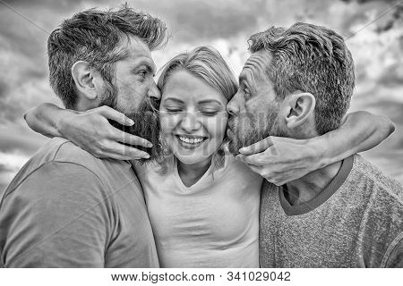 Lady enjoy romantic relations both admirers. She likes male attention. Love triangle. Men kiss same girl cheeks. Girl hugs with two guys. Romantic relations issues. Men fall in love with same woman stock photo